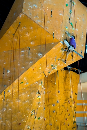 climbing sport: Sport image of climbing man (young adult) to the top of wall