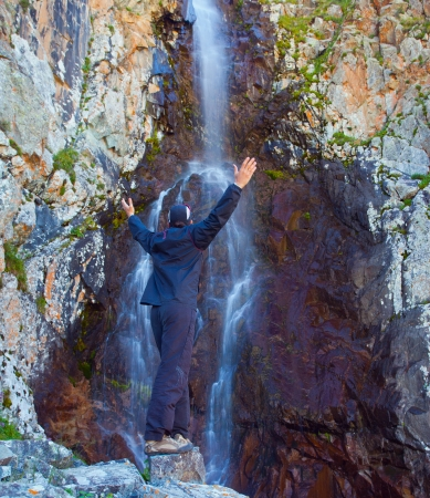 Picture of young man near a waterfall, a few meters in height and moving through the stone mountain, Ala-Archa, Kyrgyzstan. Stock Photo - 15118061