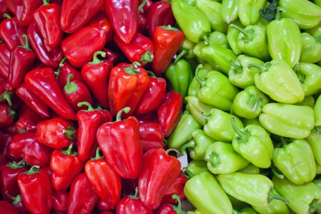 Image of a large number of fresh green and red peppers on the market. photo