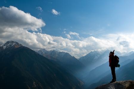 bergbeklimmen: Klimmen jonge volwassene op de top van de top met luchtfoto van de blauwe hemel Stockfoto