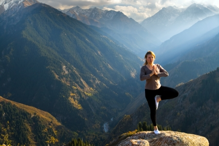 yoga rocks: Yoga at summit with aerial view of the mountain range and peak. Blue sky.