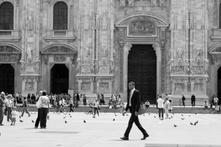 milano: MILAN, June 24, 2009: A businessman in black walking before which so many people on display at Duomo cathedral on June 24, 2009 Milan, Italy Editorial