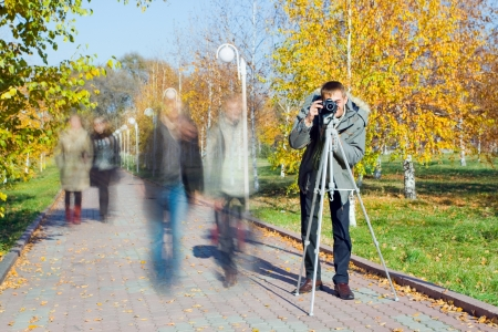 Young man taking a picture, using tripod. Motion blurred people walking in the park Stock Photo - 15117514