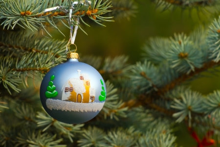 One piece of Christmas decoration of garland, on fir-tree's branch with green background having copyspace photo