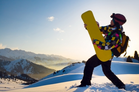 An image with playing snowboarder with a helmet and glasses on the background of high snow-capped Alps in Grindelwald, Swiss