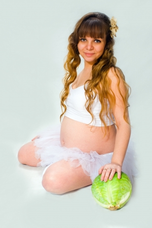 Portrait of pregnant woman with a green cabbage on a white background in the studio photo