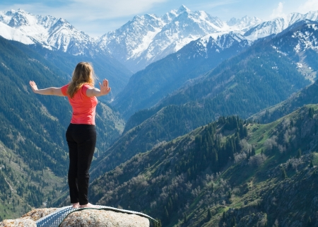 woman mountain: The young woman is doing yoga warm-up before the yoga asanas on the summit. On the background is a range of high tops of mountains.