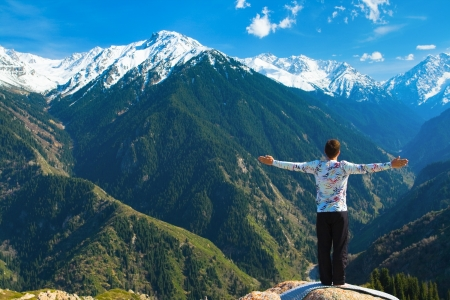 The young man is doing a yoga asana Sun Salution on the summit. On the background is a range of high tops of mountains. Zdjęcie Seryjne