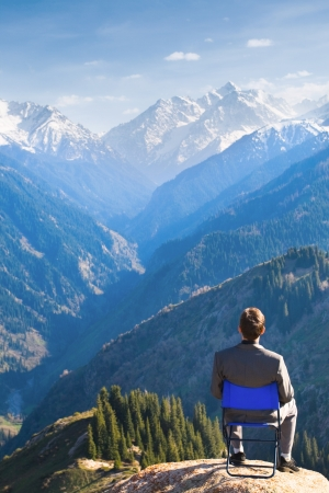 Image of a young businessman who sits on a chair at the top of the mountain and looks into the distance to the beautiful mountains, thinking about future plans. photo
