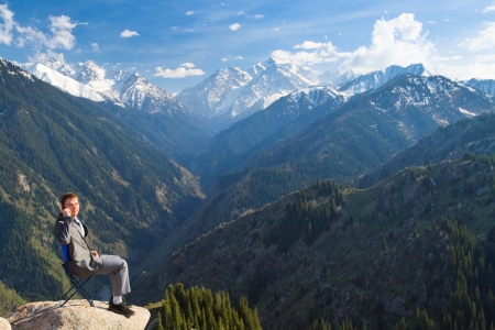 Image of a young businessman who sits on a chair at the top of the mountain and looking at the camera, talking about new idea by phone. photo