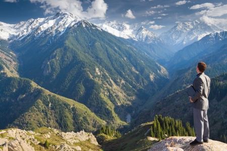 bovenaanzicht mens: Beeld van een jonge zakenman met laptop staan aan de top van de berg en op zoek naar de afstand tot de prachtige bergen, na te denken over toekomstige plannen.