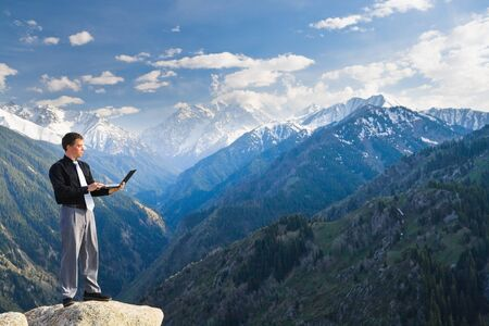 Image of a businessman standing on the top of the mountain, using a laptop. In the background a beautiful panorama of the valley with high peaks. photo