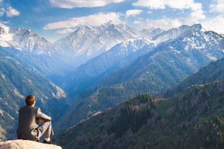 mountain view: Image of a young businessman who sits on the top of the mountain and looks into the distance to the beautiful mountains, thinking about future plans.