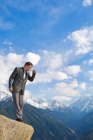 Image of a businessman standing on the top of the mountain, looking down. In the background a beautiful panorama of the valley with high peaks. photo