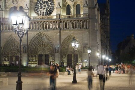 Night image of the famous cathedral of Notre-Dame in Paris against the backdrop of antique lighting lamps, France