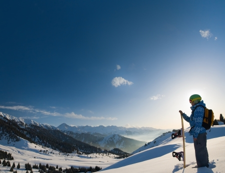 An image with a portrait of a female snowboarder wearing a helmet with a bright reflection in the glasses on the background of high snow-capped Alps in Grindelwald, Swiss