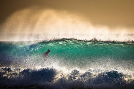 Surfer on Blue Ocean Wave in Bali, Indonesia. Focus on foreground