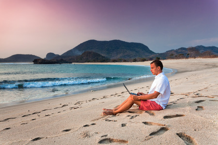 uses: man uses laptop remotely at the beach