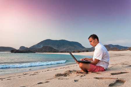 holiday trip: man uses laptop remotely at the beach