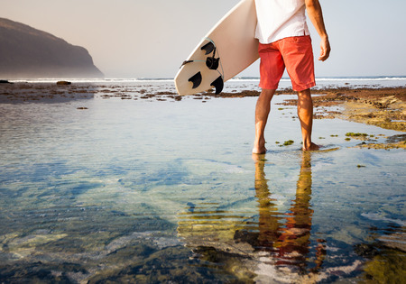 surfing waves: Surfer with surfboard on a coastline of Sumbawa, Indonesia Stock Photo