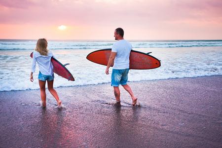 surfers: Couple of surfers walking on coast in Indonesia, Bali, Kuta