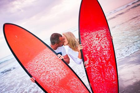 surfers: Couple of surfers kissing on coast in Indonesia, Bali, Kuta