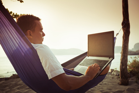 man lying on a hammock uses laptop remotely at the beach