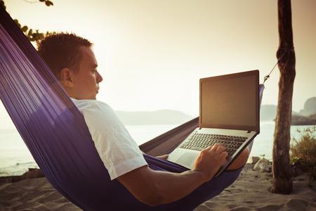 Mann auf einer Hängematte benutzt Laptop fern am Strand Standard-Bild - 38238602