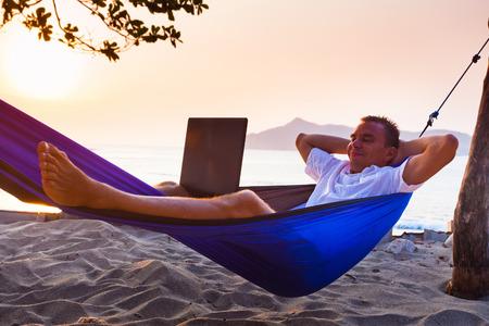 ハンモックに横になっている男はビーチでリモートでラップトップを使用してください。 写真素材