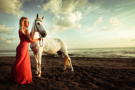 red horse: Beautiful young woman near a horse