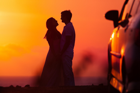 bride silhouette: Sunset background of silhouette couple, they travel by car Stock Photo