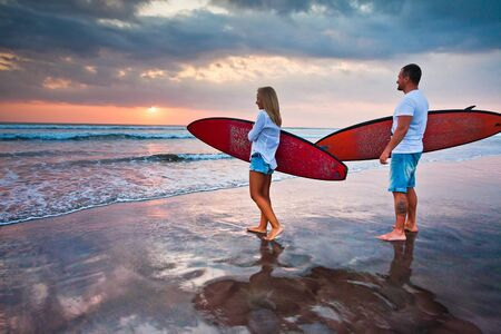 Couple of surfers walking on coast in Indonesia, Bali, Kuta