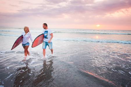 travel woman: Couple of surfers walking on coast in Indonesia, Bali, Kuta