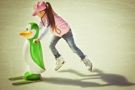 Adorable little girl in winter clothes and hat skating on ice rink at Canada