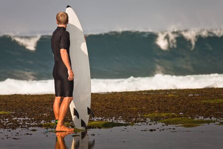 watertight: Surfer with surfboard on a coastline of Sumbawa, Indonesia Stock Photo