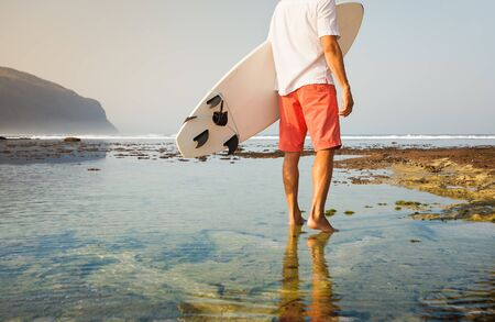 surf: Surfer with surfboard on a coastline of Sumbawa, Indonesia Stock Photo