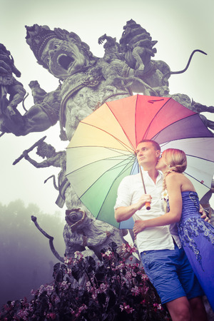 adult indonesia: Couple travelling to Asia with umbrellas in bad weather Stock Photo