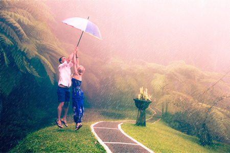 raining: Couple travelling to Asia with umbrellas in bad weather Stock Photo
