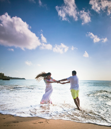 wedding couple jogging and dancing on the beach photo