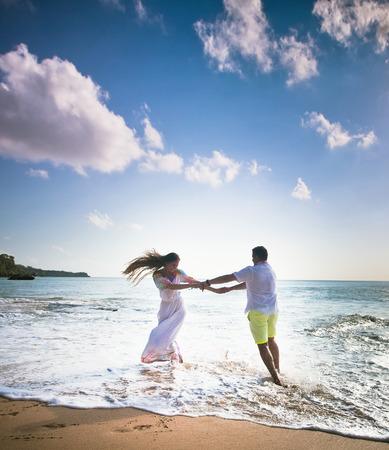 wedding couple: wedding couple jogging and dancing on the beach Stock Photo