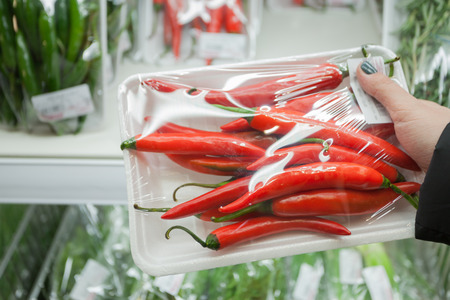 Image of packaged chili peppers with woman hand in the supermarket