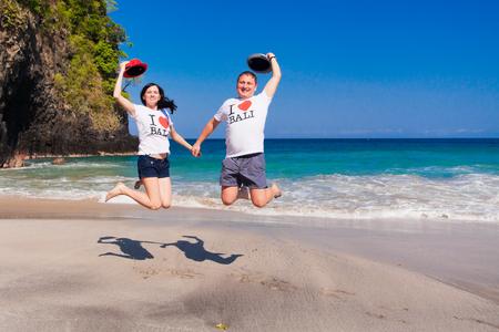 honeymooners: pareja feliz saltando en la playa con la inscripci�n en la camiseta - Me encanta Bali