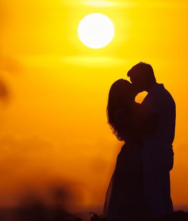enamorados besandose: pareja de amantes en el fondo de la silueta