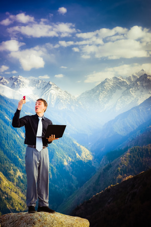 businessman standing on the top of the mountain, using a laptop and shouting into mobile phone photo