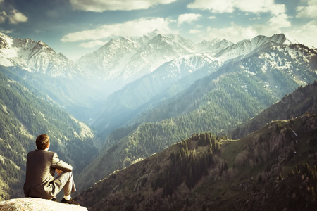 contemplate: Image of a young businessman who sits on the top of the mountain and looks into the distance to the beautiful mountains, thinking about future plans.