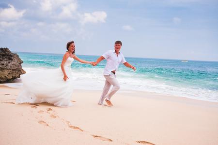 honeymooners: happy couple running at the beach Stock Photo