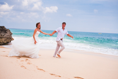honeymooners: Pareja feliz corriendo en la playa Foto de archivo