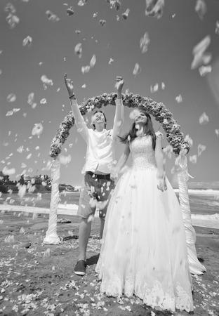 honeymooners: Old photo of wedding ceremony on the beach with happy honeymooners