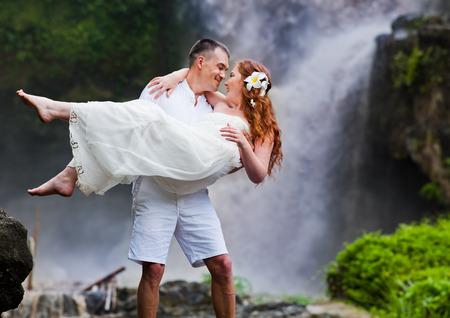 honeymooners: feliz pareja cerca de la cascada, Bali