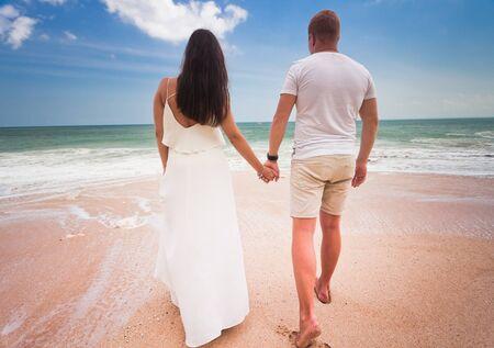 luna de miel: luna de miel pareja caminando en la playa y el cielo azul